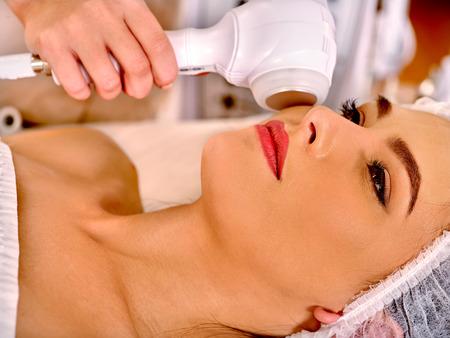 Schließen Sie oben von der jungen Frau im Hut Empfangen elektrischer Ultraschallgesichtsmassage im Beauty-Salon. Lizenzfreie Bilder