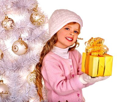 gold gift box: Child with long hair in hat and mittens holding gold  gift box near white Christmas tree. Isolated.