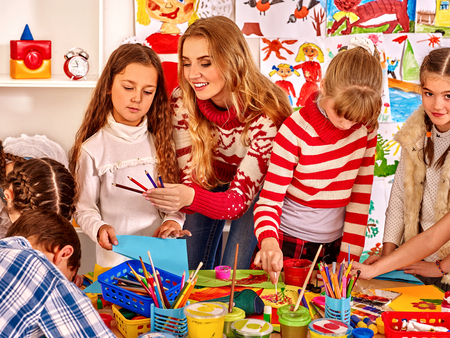 elementary: Children with young teacher  painting at art school. Education.