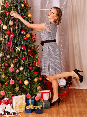 young tree: Woman dressing Christmas tree and putting gift.