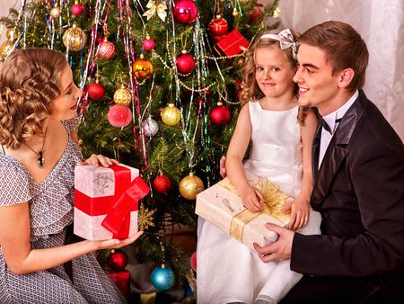 niños vistiendose: Familia con la pequeña hija que viste el árbol de Navidad. Blanco y negro retro.