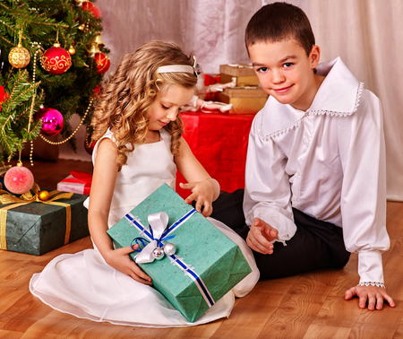 ni�os vistiendose: Children  receiving gifts under Christmas tree. Vintage style.