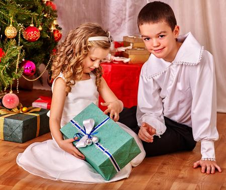 niños vistiendose: Los niños que reciben regalos bajo el árbol de Navidad. Estilo vintage.