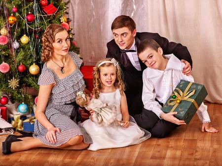 niños vistiendose: Familia feliz con los niños sentados en el suelo que recibe los regalos bajo el árbol de Navidad. Blanco y negro retro.