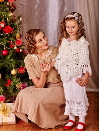 niños vistiendose: Niño femenino con el receptor madre y regalos abiertos bajo el árbol de Navidad. Estilo vintage.