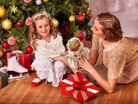 niños vistiendose: Niño con la madre de recibir regalos de la muñeca bajo el árbol de Navidad. Estilo vintage.