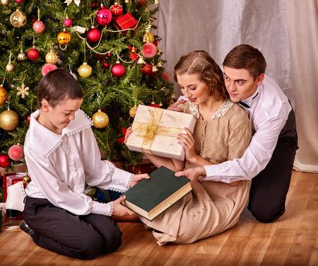 vistiendose: Familia feliz con el hijo del sentado en el suelo que recibe los regalos bajo el árbol de Navidad. Estilo vintage.