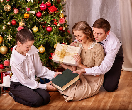 Happy family with son boy sitting on floor receiving gifts under Christmas tree. Vintage style.