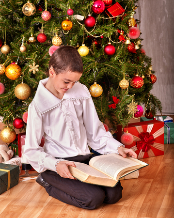 recieve: Child boy recieve book gift on Christmas tree. Vintage style.