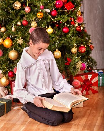 niños vistiendose: Muchacho del niño regalo libro descargar en el árbol de Navidad. Estilo vintage.