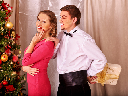 recieve: Couple on party recieve gift near Christmas tree. Vintage style.