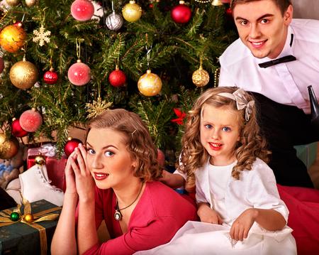 niños vistiendose: Familia con la pequeña hija que viste el árbol de Navidad. Estilo vintage. Foto de archivo