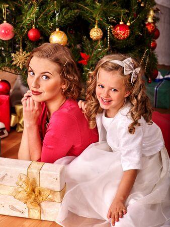 ni�os vistiendose: Ni�a ni�o con la madre que recibe cerca del �rbol de Navidad. Estilo vintage.
