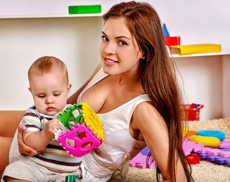 puzzle background: Kid baby boy with mother lying on floor and plying puzzle toy at home.