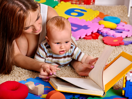 Kid baby boy with mother lying on floor and reading book at home.