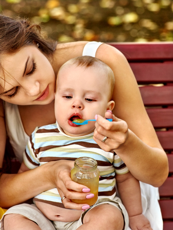 feed: Portrait of happy beautiful mother feed her baby summer outdoors in park.