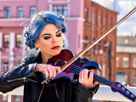 Woman performer playing violin alone. Music street.