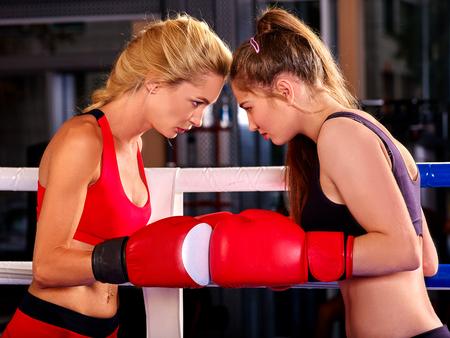 patada: Dos hermosas mujeres jóvenes boxeador con guantes rojos a la caja en el anillo. Foto de archivo
