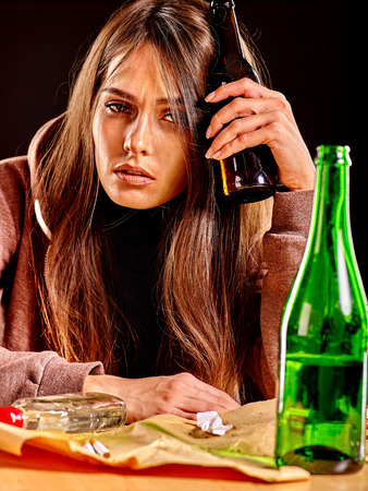 drunk girl: Drunk girl holding green bottle of alcohol. Soccial issue alcoholism. Stock Photo