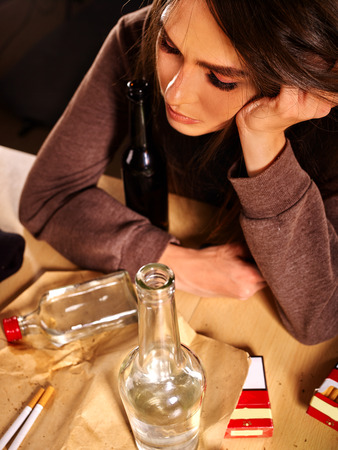 drunk girl: Drunk girl sitting with bottle of alcohol. Soccial issue female alcoholism.