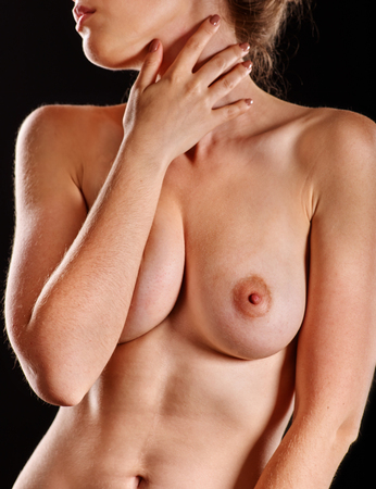 Portrait of young woman with beautiful nude topless breasts and lips on dark background. Stock Photo
