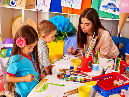 Children with teacher woman painting on paper at table  in  kindergarten . Group people. Imagens - 48201235
