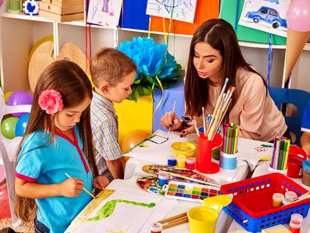 Kinder mit Lehrer Frau Malerei auf Papier am Tisch im Kindergarten. Gruppe Menschen.