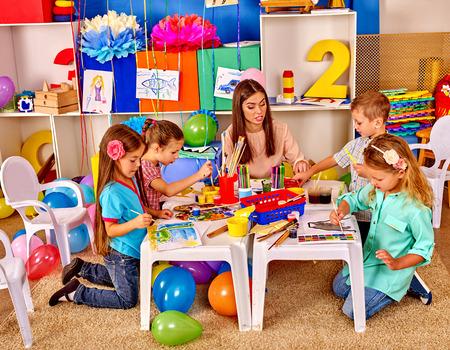 maestra preescolar: Los niños con la mujer del profesor aprender pintura sobre papel a la mesa en el jardín de infantes.