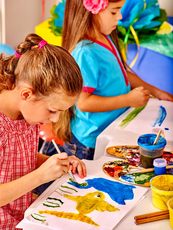 kinder: ni�as del grupo cepillo sobre la mesa en el jard�n de infantes pintura.