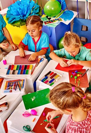 kinder: niños del grupo moldeados de la mesa de plastilina en el jardín de infantes. Vista superior.