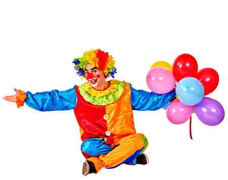 birthday clown: Happy birthday clown holding a bunch of balloons sitting on floor.  Isolated. Stock Photo