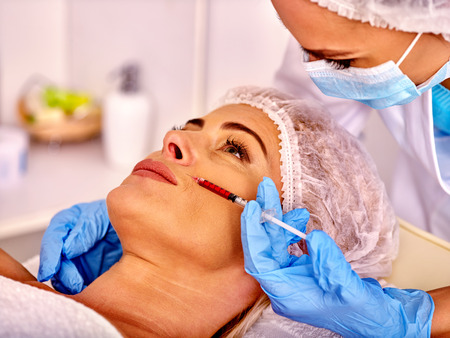 Woman middle-aged in spa salon with beautician. Female giving lips botox injections.