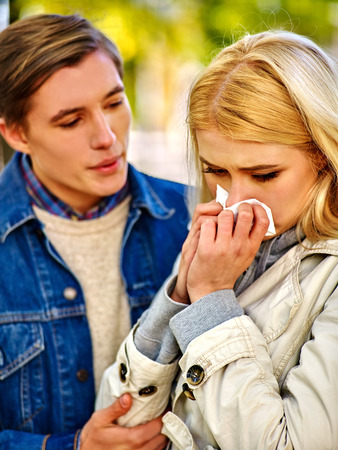 cold season: Woman with cold rhinitis on autumn outdoor. Fall flu season. Man looks with compassion on suffering of loved one. Autumn park outdoor. Stock Photo