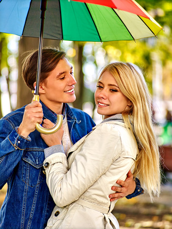 couple in rain: Happy young couple embracing under colourful umbrella in autumn day. Love relationships concept .