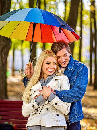 couple in rain: Happy young couple cudling under umbrella on bench in autumn day. Love and couple relationships concept and idea. Stock Photo