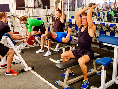 uomini belli: Group of people strong and handsome men working with  dumbbells his body at gym.