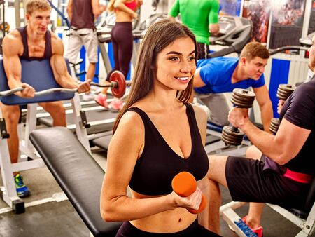 heavy weight: Group of people men and beautiful girls working with  dumbbells his body at gym. Stock Photo