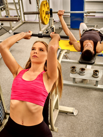 lifestyle woman: Woman working his arms and chest at gym. Bicep curl machine. Stock Photo