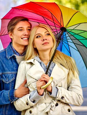 sotto la pioggia: Felice giovane coppia che abbraccia sotto l'ombrello nel giorno di autunno e guardando in alto sul cielo.
