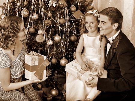 niños vistiendose: Familia con bonita pequeña hija que viste el árbol de Navidad. Blanco y negro de la vendimia retro.