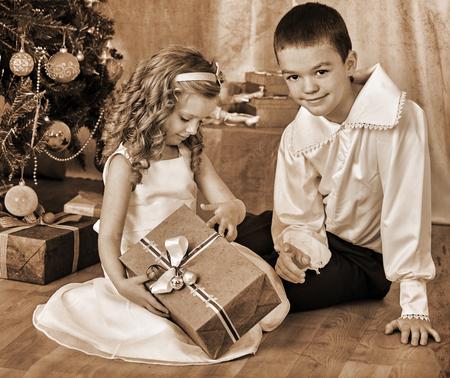 niños negros: Niños felices hermano y hermana regalos abiertos bajo el árbol de Navidad. Blanco y negro de la vendimia retro.