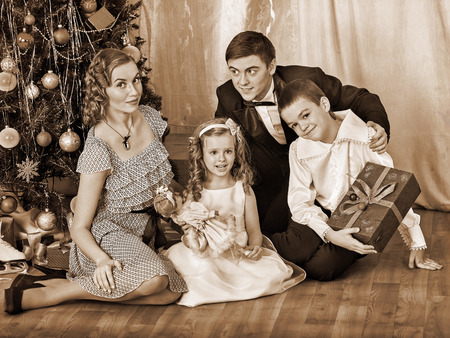 niños vistiendose: Familia feliz con los niños y regalos hermosos padre que recibe bajo el árbol de Navidad. Blanco y negro retro