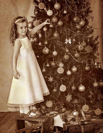 ni�os vistiendose: Little girl at chair decorate on Christmas tree. Black and white retro vintage. Foto de archivo