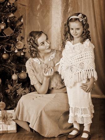 niños vistiendose: Hija y madre amorosa que recibe cerca del árbol de Navidad. Blanco y negro de la vendimia retro.