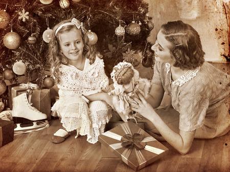 niños vistiendose: Muchacha con la madre que recibe los regalos viejos Muñeco recostado bajo el árbol de Navidad. Blanco y negro de la vendimia retro.