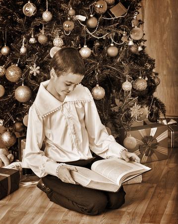 niños vistiendose: Muchacho bajo el árbol de Navidad leer libro viejo. Blanco y negro de la vendimia retro.