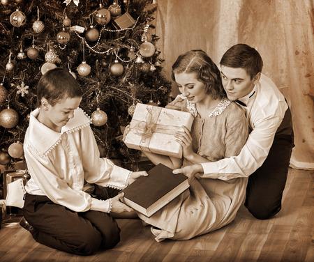 niños vistiendose: Boy recibir libro de regalo y otros regalos de su familia bajo el árbol de Navidad. Blanco y negro de la vendimia retro.
