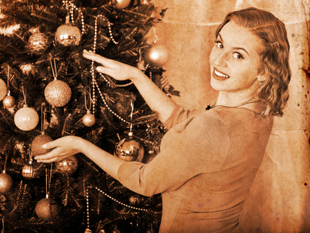 retro lady: Smiling young woman dressing Christmas tree at home. Black and white vintage.