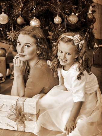 ni�os vistiendose: Child with mother waiting father near Christmas tree. Black and white retro vintage.
