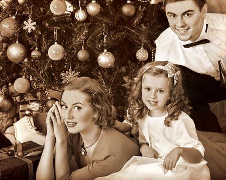 niños vistiendose: Familia con hijos, madre y padre que viste el árbol de Navidad. Blanco y negro de la vendimia retro.